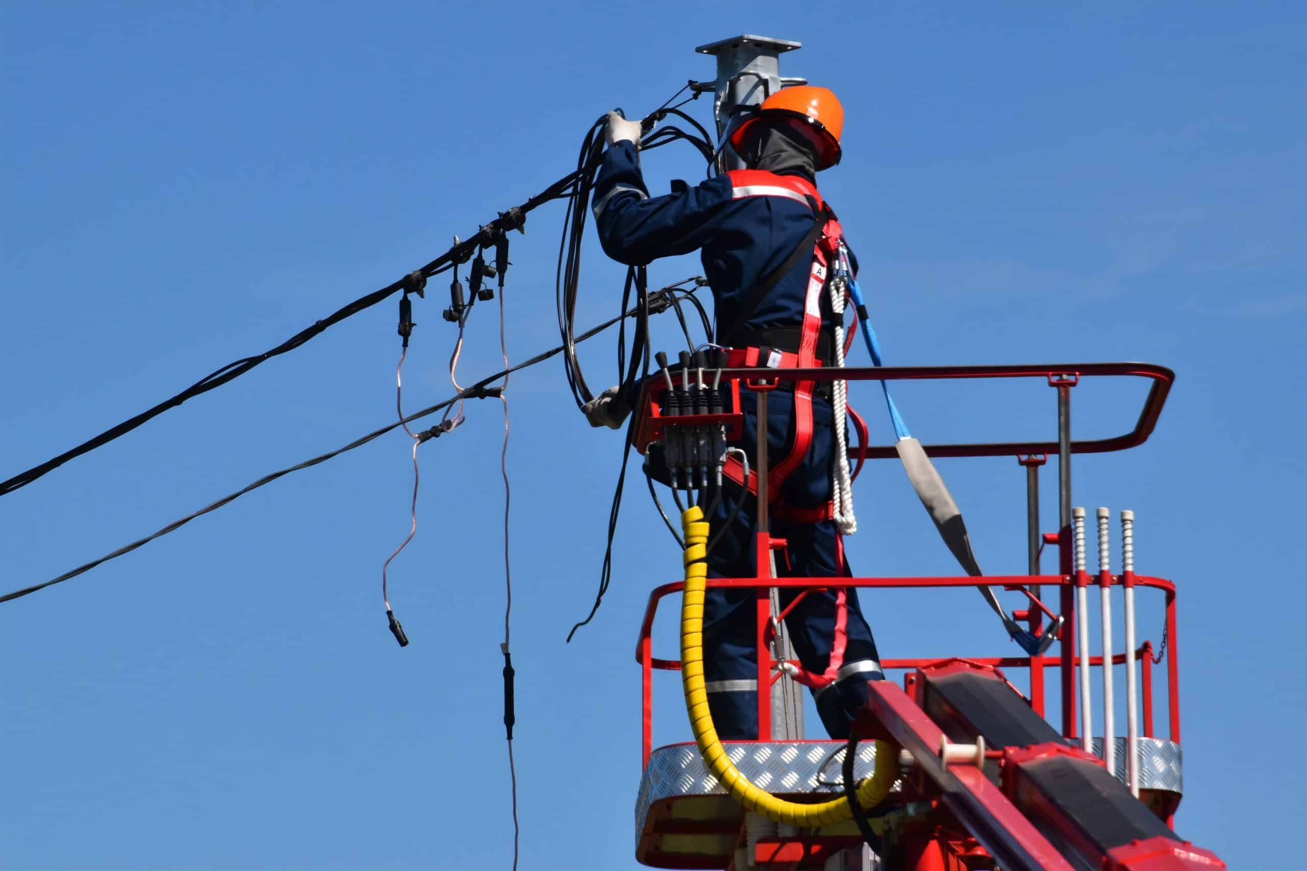 Utility worker fixing electricity power lines