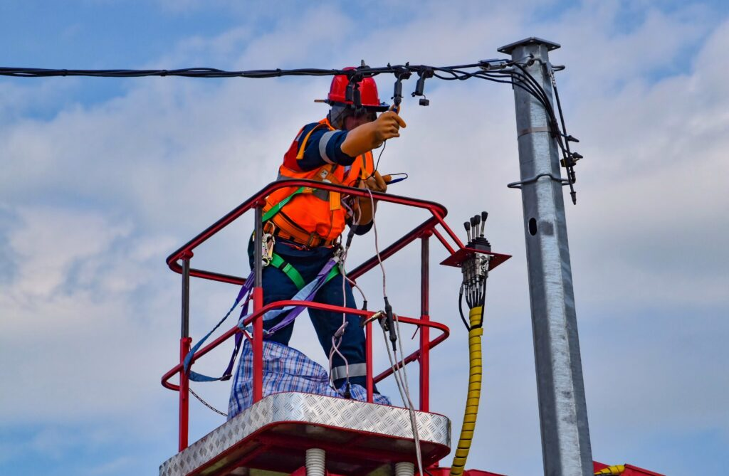 Utility worker maintaining transmission line